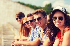 Fermez-vous des amis de sourire s'asseyant sur la rue de ville Image libre de droits