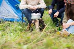 Fermez-vous des amis faisant cuire la nourriture dans le dixie au camp Image stock