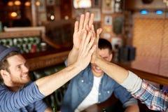 Fermez-vous des amis faisant la haute cinq à la barre ou au bar Photo stock