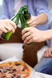 Fermez-vous des amis faisant tinter des bouteilles à bière à la maison Photos libres de droits