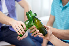 Fermez-vous des amis faisant tinter des bouteilles à bière à la maison Image stock