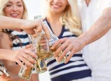 Fermez-vous des amis faisant tinter des bouteilles avec des boissons Images stock