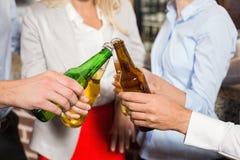 Fermez-vous des amis grillant avec des bouteilles de bière Image stock
