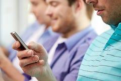 Fermez-vous des amis heureux avec des smartphones à la maison Photo stock