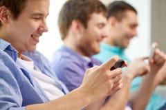 Fermez-vous des amis heureux avec des smartphones à la maison Photographie stock libre de droits