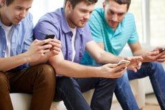 Fermez-vous des amis heureux avec des smartphones à la maison Photos libres de droits