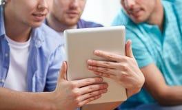 Fermez-vous des amis heureux avec le PC de comprimé à la maison Image libre de droits