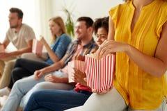 Fermez-vous des amis heureux mangeant du maïs éclaté à la maison Images stock