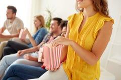 Fermez-vous des amis heureux mangeant du maïs éclaté à la maison Photographie stock libre de droits