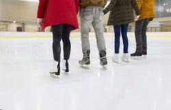 Fermez-vous des amis heureux patinant sur la patinoire Photographie stock libre de droits