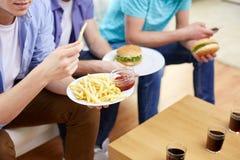 Fermez-vous des amis mangeant des aliments de préparation rapide à la maison Photo stock