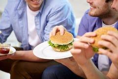 Fermez-vous des amis mangeant des hamburgers à la maison Photo libre de droits