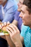 Fermez-vous des amis mangeant des hamburgers à la maison Image libre de droits
