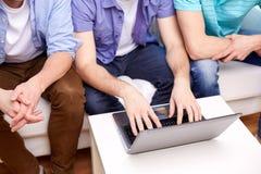 Fermez-vous des amis masculins avec l'ordinateur portable à la maison Photo stock