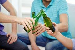 Fermez-vous des amis masculins buvant de la bière à la maison Photo stock