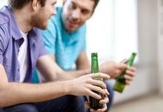 Fermez-vous des amis masculins buvant de la bière à la maison Photos stock