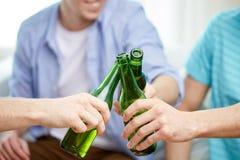 Fermez-vous des amis masculins buvant de la bière à la maison Image stock
