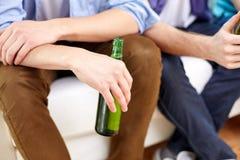 Fermez-vous des amis masculins buvant de la bière à la maison Photo libre de droits