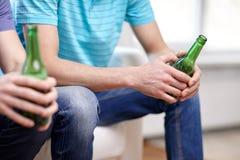Fermez-vous des amis masculins buvant de la bière à la maison Images stock