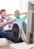 Fermez-vous des amis masculins heureux regardant la TV à la maison Photo stock