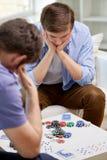 Fermez-vous des amis masculins jouant des cartes à la maison Image stock