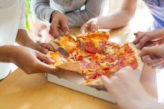 Fermez-vous des amis ou des personnes mangeant de la pizza Photos stock