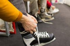 Fermez-vous des amis portant des patins sur la piste de patinage Photo libre de droits