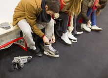 Fermez-vous des amis portant des patins sur la piste de patinage Images libres de droits