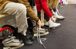 Fermez-vous des amis portant des patins sur la piste de patinage Photo stock