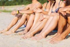 Fermez-vous des amis s'asseyant sur la plage d'été Photos stock