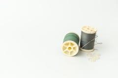 Fermez-vous des articles de couture, de la bobine du fil, de l'aiguille et du bouton Image stock