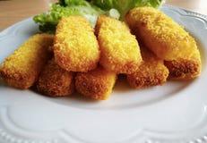 Fermez-vous des bâtons de poissons du plat blanc avec des légumes de culture hydroponique sur le fond Photographie stock