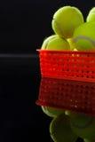 Fermez-vous des balles de tennis jaunes fluorescentes dans le panier en plastique avec la réflexion photos stock