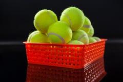 Fermez-vous des balles de tennis jaunes fluorescentes dans le panier en plastique rouge avec la réflexion images stock