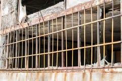 Fermez-vous des barres de sécurité en métal sur les fenêtres des murs endommagés de petite maison avec des trous de balle utilisé photo stock