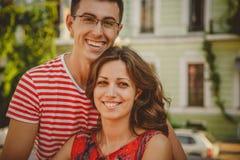 Fermez-vous des beaux jeunes couples de sourire dans l'amour, étreindre, se tenant derrière l'un l'autre dehors à la rue de ville Photographie stock