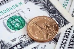 Fermez-vous des billets de dollar US et d'une pièce du dollar photo libre de droits