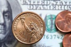 Fermez-vous des billets de dollar US et d'une pièce du dollar photographie stock
