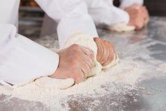 Fermez-vous des boulangers malaxant la pâte au compteur image stock