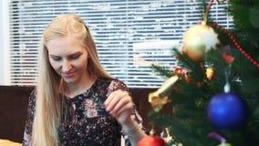 Fermez-vous des boules accrochantes de sourire de fille sur l'arbre de Noël banque de vidéos