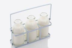 Fermez-vous des bouteilles à lait dans le support sur le fond blanc Image stock