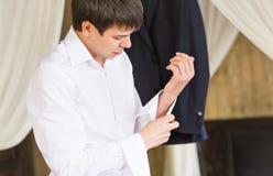 Fermez-vous des boutons de manchette de port d'homme d'affaires Jeune homme élégant d'affaires de mode image stock