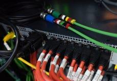 Fermez-vous des câbles de réseau reliés au commutateur photo stock