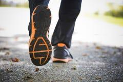 Fermez-vous des chaussures de course sur l'asphalte Image stock