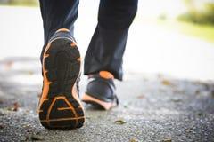 Fermez-vous des chaussures de course sur l'asphalte Photographie stock libre de droits
