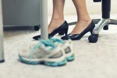 Fermez-vous des chaussures de sports d'une femme d'affaires dans un bureau Images libres de droits