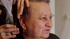 Fermez-vous des cheveux de coupe de coiffeur Mains de femme adulte heureuse de coiffeur professionnel banque de vidéos