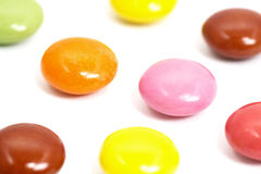 Fermez-vous des chocolats colorés sur le fond blanc Photo libre de droits