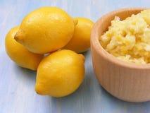 Fermez-vous des citrons sur un fond en bois bleu avec la purée des citrons dans le pot en bois Photo libre de droits