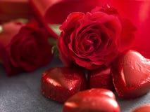 Fermez-vous des coeurs de chocolat et des roses rouges Rose rouge Photographie stock libre de droits
